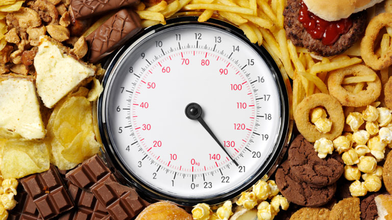 Various high-fat foods and a weighing scale