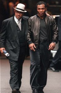 Honeyghan [left] walks alongside Mike Tyson in London, 2000.