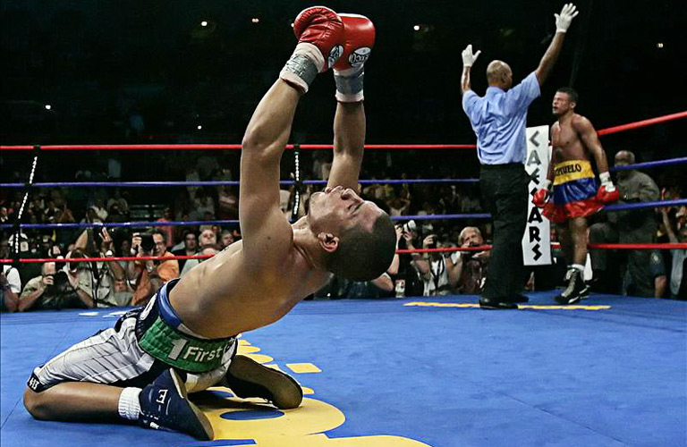 WBO junior welterweight champion Miguel Cotto from Puerto Rico (L) celebrates his title defense over Ricardo Torres (R) from Magangue, Columbia, as referee David Fields stops the fight during the seventh round in Atlantic City, New Jersey, September 24, 2005